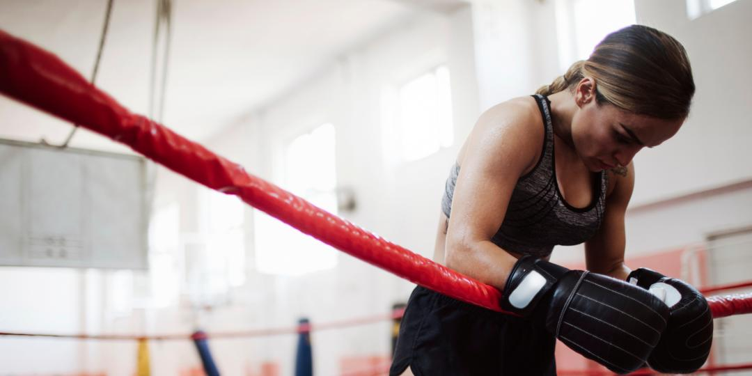 A woman in boxing gloves leaning over the ropes of a ring with her head down as if recovering from a tough workout